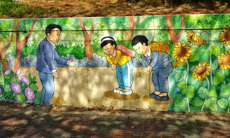 Jeju island, South Korea - April 2018: Students with knapsacks are greeted by the teacher's bow. Retro drawings from the life of old-school students on the wall of the school in Jeju.