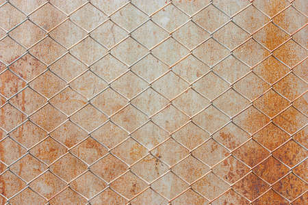 Steel mesh behind the rusted iron sheets.