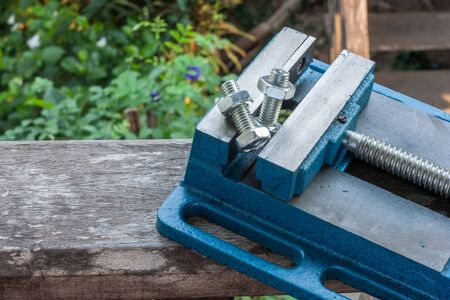 carpenter vise: nut and bolt under the Pressure of Vice on nature background Stock Photo