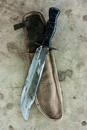 sheath: Large knife on sheath on the cement floor of old. Stock Photo