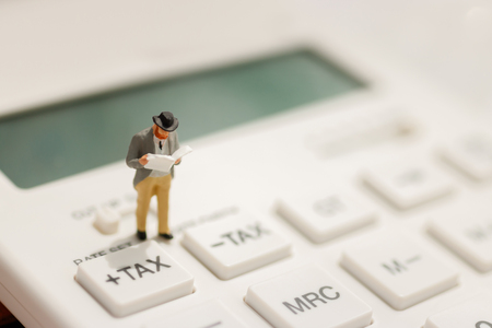 Miniature businessman stand reading on tax button of calculator,  education, financial and business concept.  Stockfoto