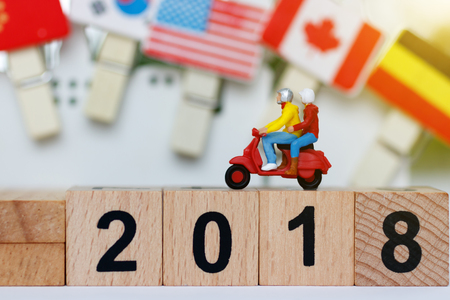 Miniature traveler with motorcycle on the wood block with number 2018. Travel  concept. Archivio Fotografico
