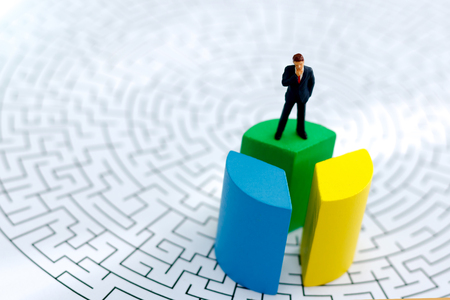 Miniature people: Businessman standing on top wooden block with maze. Business management concept