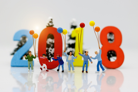Miniature people, children with colorful balloons standing in front of number 2018, Family concept.