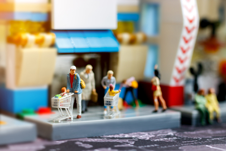 Miniature people family with shopping cart in supermarket, Tourism, shopping or business concept.  Stock Photo
