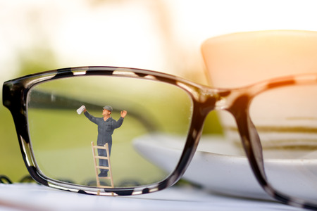 Miniature people worker cleaning eyes glasses. Business concept 스톡 콘텐츠