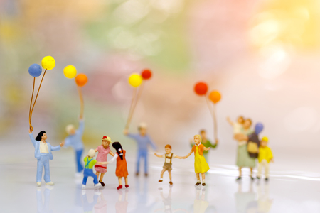 Miniature people, family and children with colorful balloons standing in front of house, Family concept.