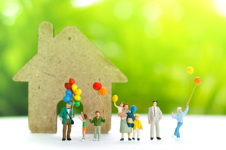 Miniature people with family holding balloon  with  home, happy family day concept.