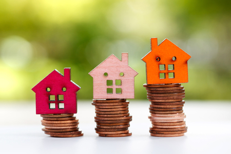 Modello di casa in legno sulla pila di monete. Proprietà, finanza, investimenti e crescita nel concetto di business.