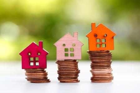 Modelo de casa de madera en pila de monedas. Propiedad, finanzas, inversión y crecimiento en el concepto de negocio.