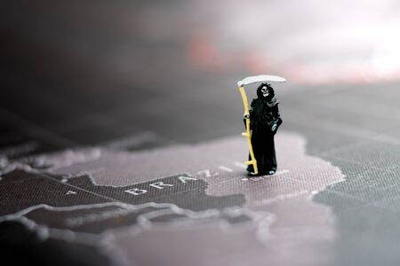 Miniature: Demon of death standing on black map using as background.  Stock Photo