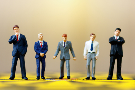 miniature businessmen standing on the dartboard. Target business concept.