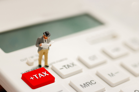 Tax Concept with miniature businessman reading on calculator.