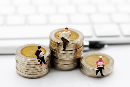 Miniature people reading and sitting on coins stack with keyboard, education or business concept.