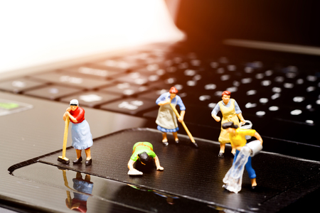 Miniature women cleaning  pointing device laptop. Concept of cleaning viruses computer, security and technology .