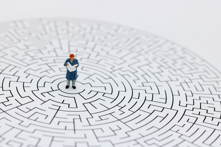 Miniature people: Businessman reading on center of maze. Concepts of finding a solution, problem solving and challenge. Stock Photo