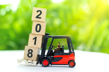 Miniature worker transporting wooden block with number 2017, Business or transportation  concept.