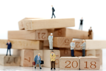 Miniature business people sitting on wood block with number 2018, recruitment finding employee and business concept. Stock Photo
