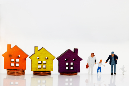 Miniature people with family walking hand in hand  with houses on coin stack, happy family day concept.