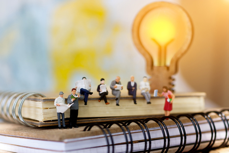 Miniature people reading and sitting on book with lamp idea using as background, education or business concept.