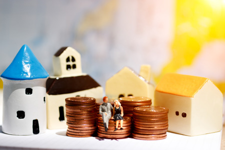 Miniature people sitting on step of coin money with home. Finance, investment and growth in business concept.