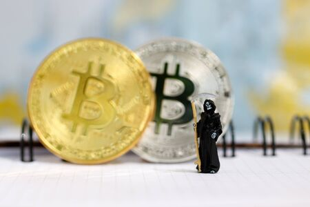 Miniature: Demon of death standing with bitcoin. Financial and business concept.   Stock Photo