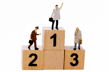 Miniature people: Businessman standing on wooden podium 1,2,3 with business team competition concept. 免版税图像