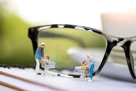 Concept of tourism, shopping or business. Miniature people family with shopping cart on book.  Stock Photo
