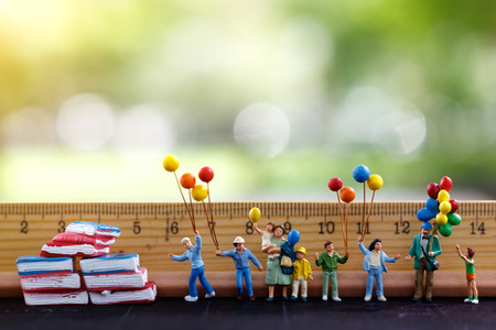 Miniature people, family and children standing hold colorful balloons  with ruler and books. Education, business and Family concept. Standard-Bild