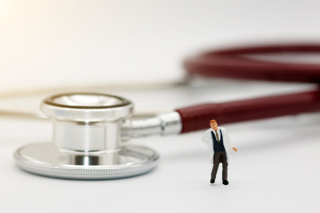 Miniature people: Doctor standing with stethoscope, Medical  and business concept.