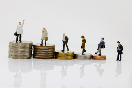 Miniature businessman standing on stack of coin. Money, business and finance investment concept