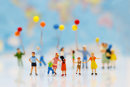 Miniature people, family and children with colorful balloons standing in front of house, Family concept. Stock Photo