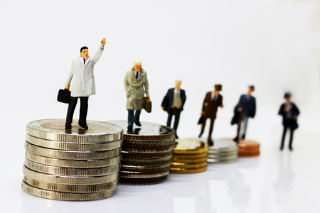 Miniature businessman walking on step of coin money. Finance and growth in business concept