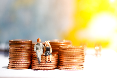 Miniature people sitting on step of coin money. Finance, investment and growth in business concept.