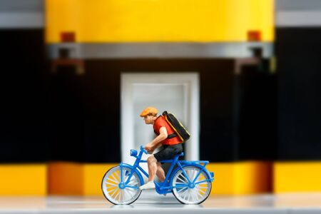 Miniature traveler riding bicycle with sports shop. Travel and Sport concept. Banque d'images