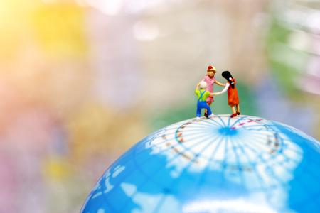 Playful children holding hands on globe.