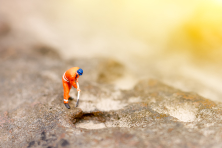 Miniature people: Male miner in uniform pickaxe the stones. Stock Photo
