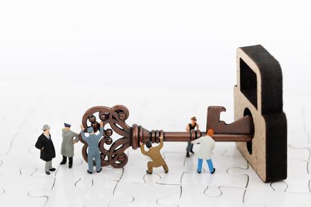 miniature people teamwork helps to unlock the keys. Business team concept.