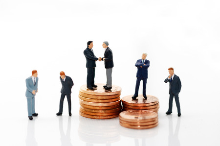 Miniature people: Businessman handshake with coins stack.  Investment, agreement, partnership and business concept