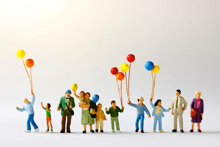 Miniaturleute mit der Familie, die Ballon auf der Karte mit Sonnenlicht, glückliches Familientageskonzept hält. Standard-Bild