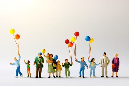 Miniature people with family holding balloon  on the map with sunlight, happy family day concept. Standard-Bild