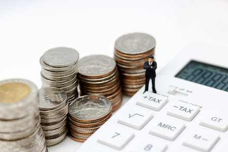 Miniature people, businessman standing with calculator and coins money,  tax, financial and business concept. Stockfoto