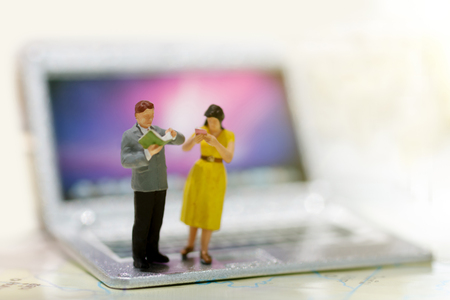 Miniature people reading book on laptop, education or  business concept.