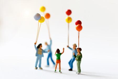 미니어처 사람들이 햇빛, 행복 한 가족 하루 개념 풍선을 들고 아이들. 스톡 콘텐츠