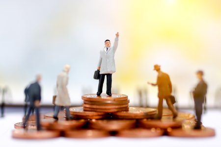 Miniature business people standing on step of coin money. Finance, investment and growth in business concept.