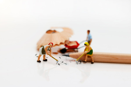Miniature people cleaning pencil scrap. Concept of cleaning day.