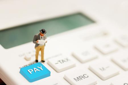 Betalen en bedrijfsconcept. Miniatuur zakenmanlezing op calculator Stockfoto