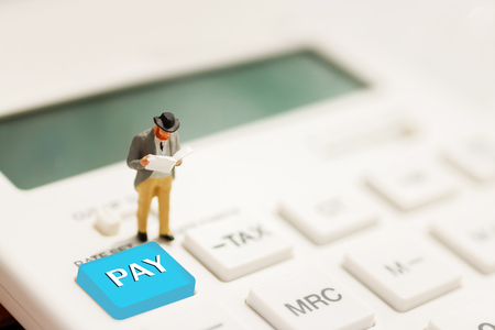 Pay and business concept. Miniature businessman reading on calculator