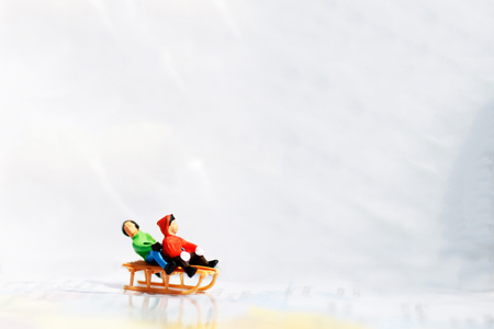 Miniature kids playing fun with snow slider.