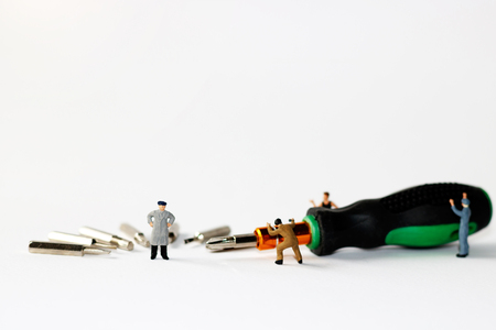 Miniature people: Worker with Craftsman tool, screwdriver. Stock Photo